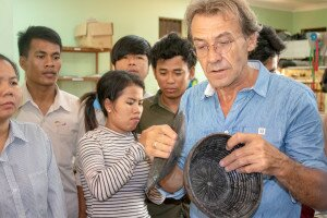 Master lacquerer explaining traditional uses of lacquer during practical training session.