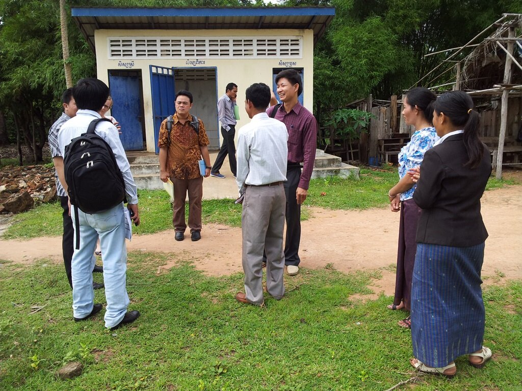 The delegates and school principal and hygiene teacher talking about school sanitation and hygiene